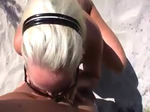 Horny blonde sucking and fucking at a public beach
